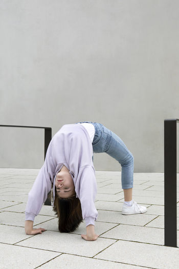 Full length of woman relaxing on floor against wall