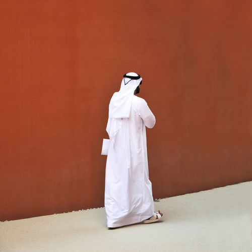 Full Length Of Man In Traditional Clothing Walking By Red Wall