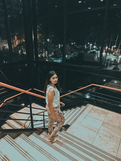 Full length portrait of young woman moving down on steps at night
