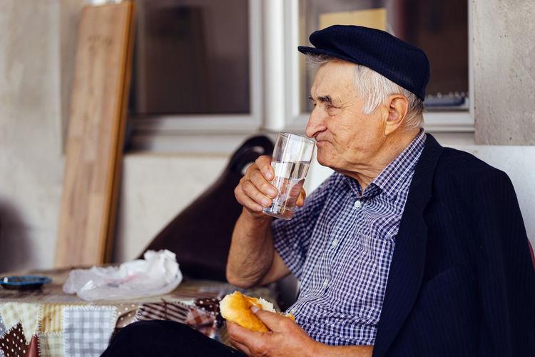 Senior man having food and drink while sitting on seat