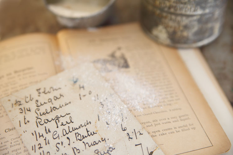 High angle view of recipe on paper by flour on book
