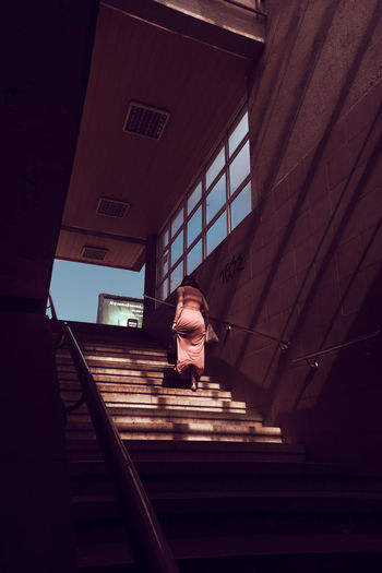 Low angle view of man walking on staircase in building
