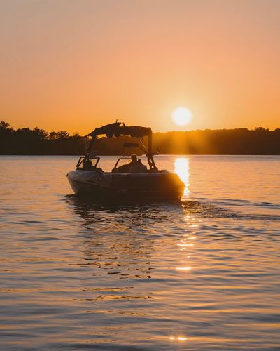 Silhouette boat in lake against sky during sunset