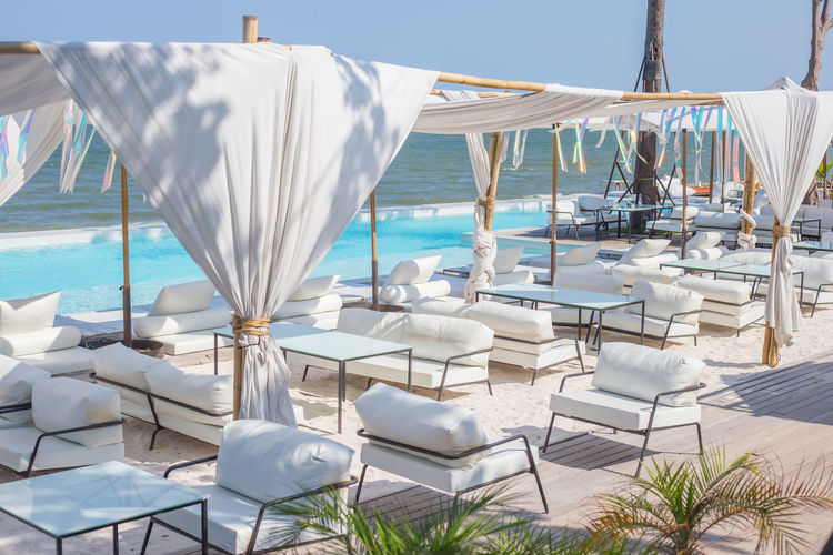 Lounge chairs and tables by infinity pool against sky