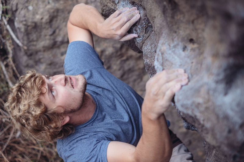 High Angle View Of Young Man Climbing Rock