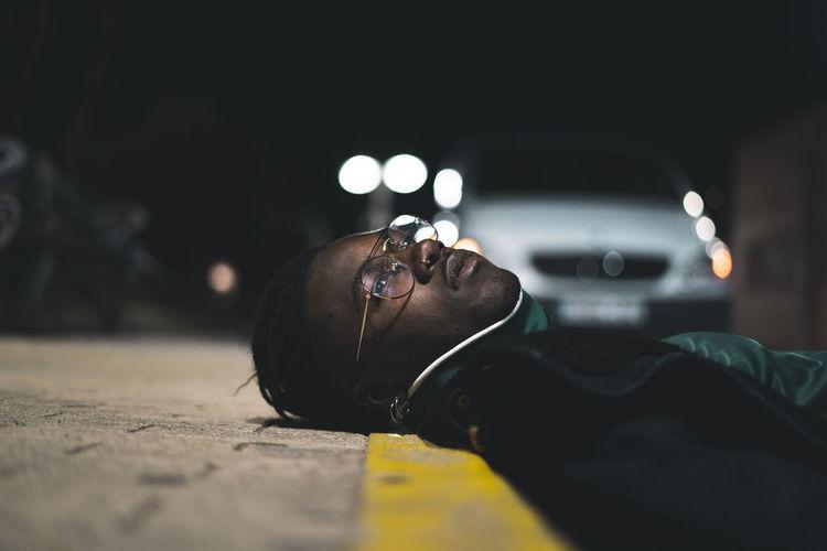Portrait of man lying down on street