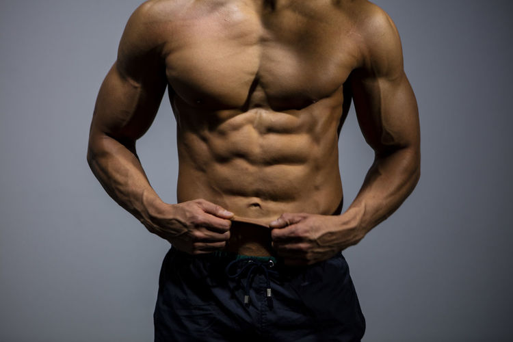 Midsection Of Muscular Man Standing Against Gray Background