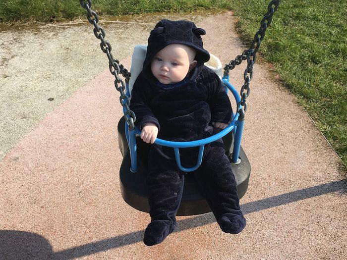 High angle view of cute baby sitting on swing