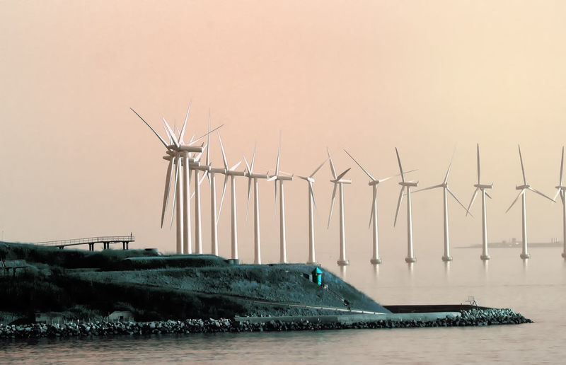 Wind turbines in river against clear sky at sunset