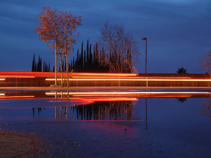 Light trails by lake against blue sky at dusk
