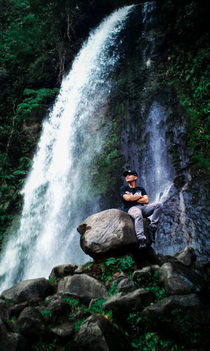 Scenic view of waterfall with man sitting on rock in forest