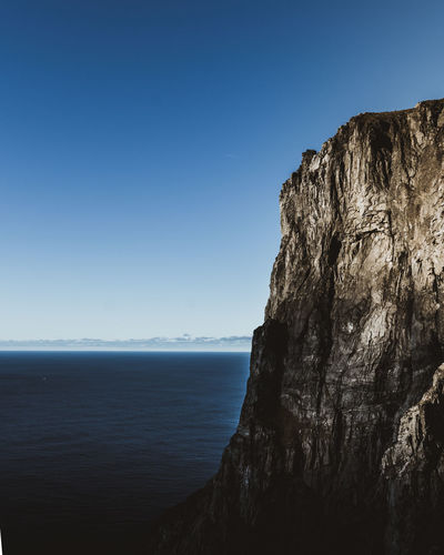 Scenic view of sea and cliff against clear blue sky