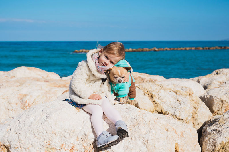 Portrait of cute girl with dog sitting on rock