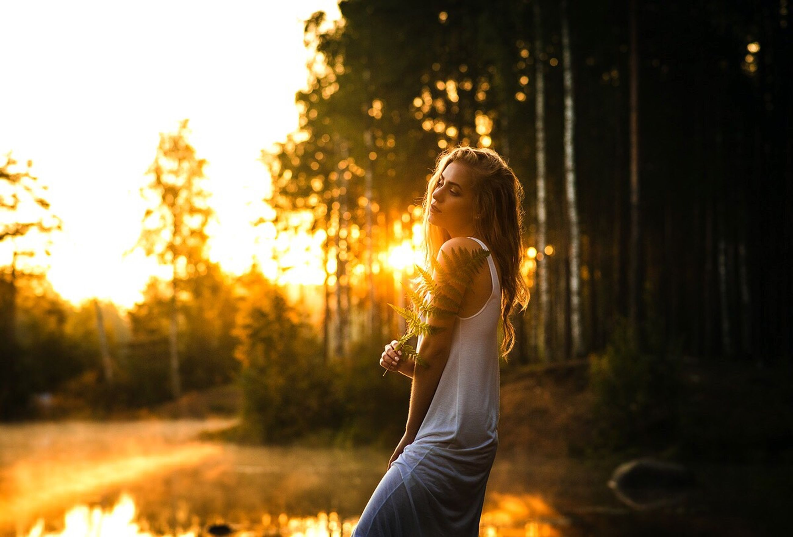 lifestyles, leisure activity, lens flare, sunset, sun, focus on foreground, sunbeam, casual clothing, outdoors, nature, sky, back lit, selective focus, orange color, plant, tranquility, illuminated, grass, growth, beauty in nature