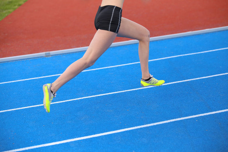 Low section of woman running on track