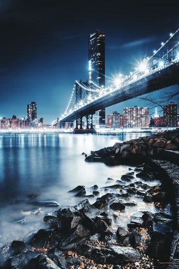 Low angle view of illuminated manhattan bridge over river at night