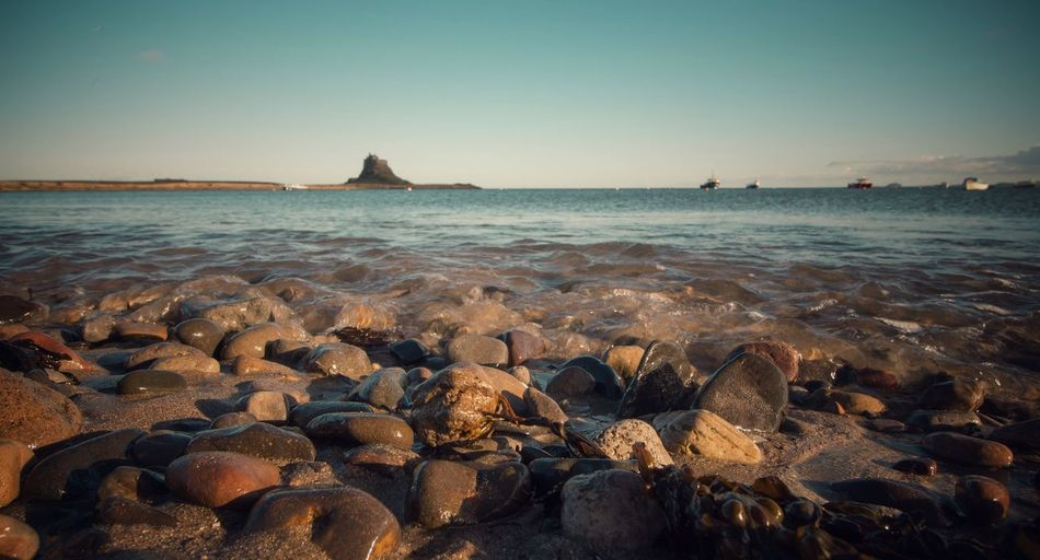 high tide holy island Beach Beauty In Nature Clear Sky Horizon Over Water Pebble Rock - Object Sea Shore Tranquil Scene Water