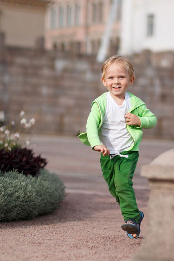 Portrait of smiling boy running outdoors