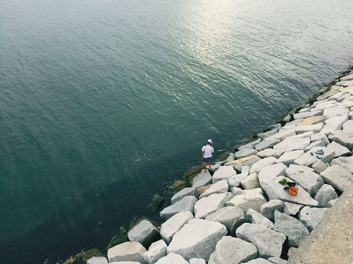 High Angle View Of Man Standing On Rocks By Sea