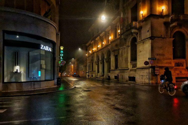 Wet street amidst illuminated buildings in city during rainy season