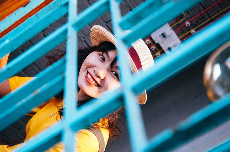 Portrait of smiling young woman seen through fence