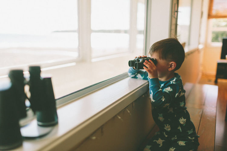 A little boy looking out of the window with binoculars. Child Boy Binoculars Curious Adventure Explore Searching Looking Out Of The Window