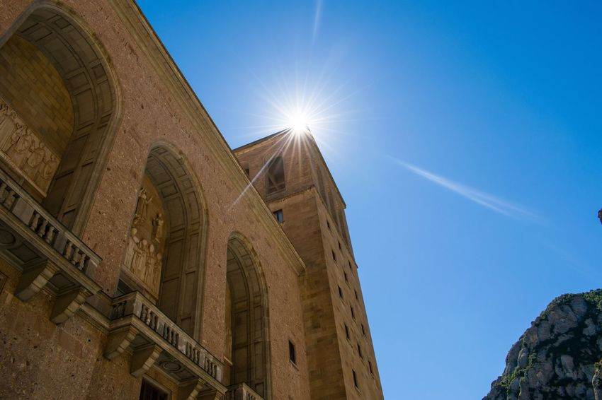 Sunbeam Sun Low Angle View Blue Sunlight Architecture Clear Sky Lens Flare Built Structure Building Exterior Sunny Bright History Arch Travel Destinations Sky Day Majestic Tourism Outdoors Barcelona Montserrat Monastery Star Sun