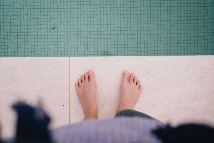 Low section of man legs in swimming pool