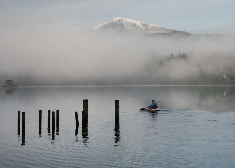 Man kayaking on lake against mountain during foggy weather