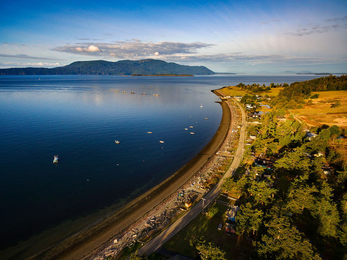Sunrise on Legoe Bay, Lummi Island, Washington. On the west side of Lummi Island the view is towards nearby Orcas Island and the reefnet salmon fishing boats anchored in Legoe Bay. Drone  Fishing Boats Lummi Island Orcas Island Salish Sea Sunny Washington Aerial Bay Beach Driftwood High Angle View Island No People Reefnet Road San Juan Islands Scenics - Nature Sea Shoreline Sky Summer Sunrise Water Waterfront