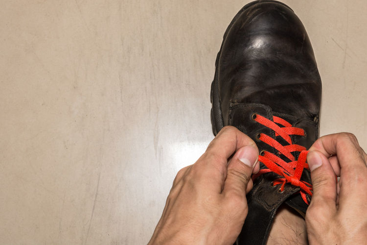 Cropped hand of man tying shoelace on floor