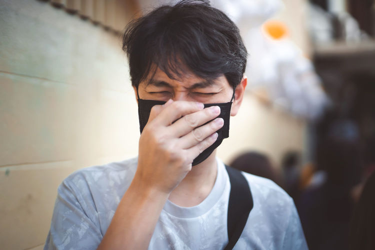 Close-up of man wearing mask coughing outdoors