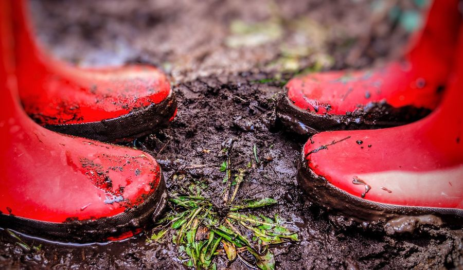 Close-Up Of Red Rubber Boots On Dirt