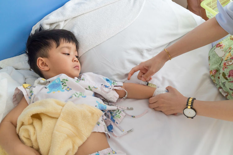 High Angle View Of Doctor Holding Syringe By Baby Boy