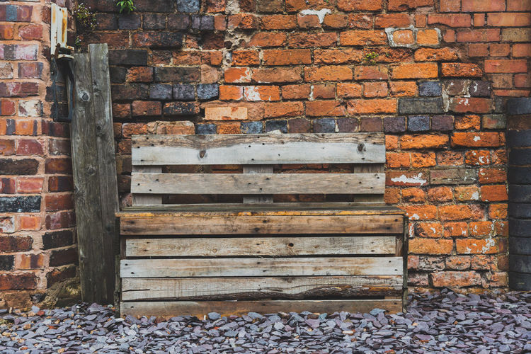 wooden pallets stacked up on stone by a brick wall Birmingham Brick Brick Texture Brick Wall Bricks Building Materials Day Digbeth No People Orange Color Outdoors Outside Pallet Pallets Uk Wood Wooden Bench Wooden Pallet Wooden Post