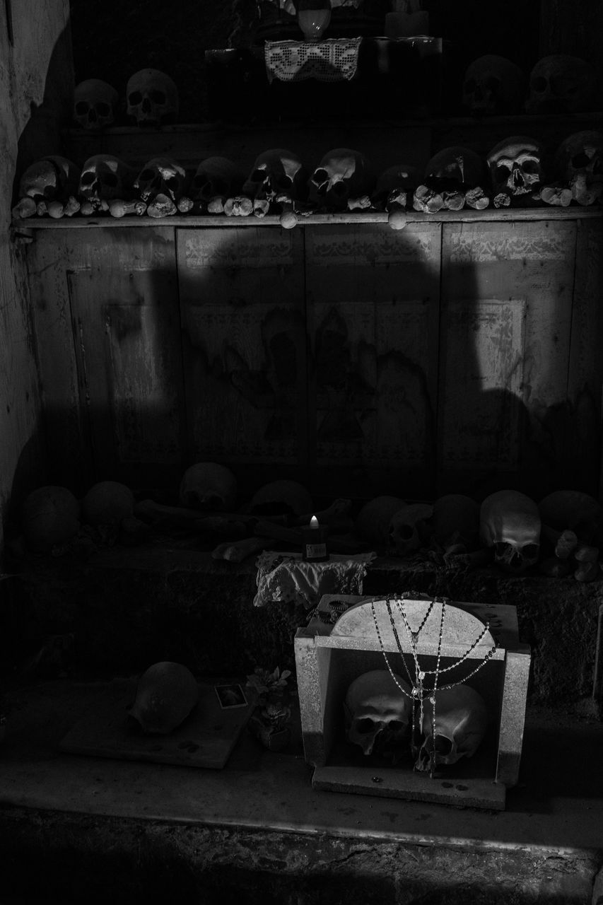 no people, indoors, container, architecture, old, table, still life, large group of objects, building, furniture, built structure, abandoned, spooky, group, art and craft, religion, bottle, candle, human representation, close-up