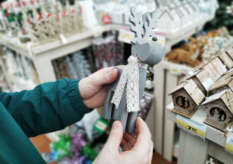Cropped hand of young man holding christmas decoration at store