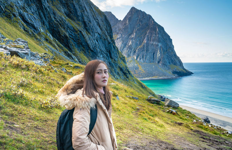 Portrait of woman standing by sea against mountains