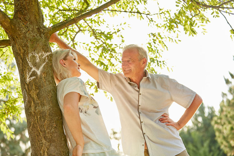 Senior Man Looking At Woman While Standing Against Tree