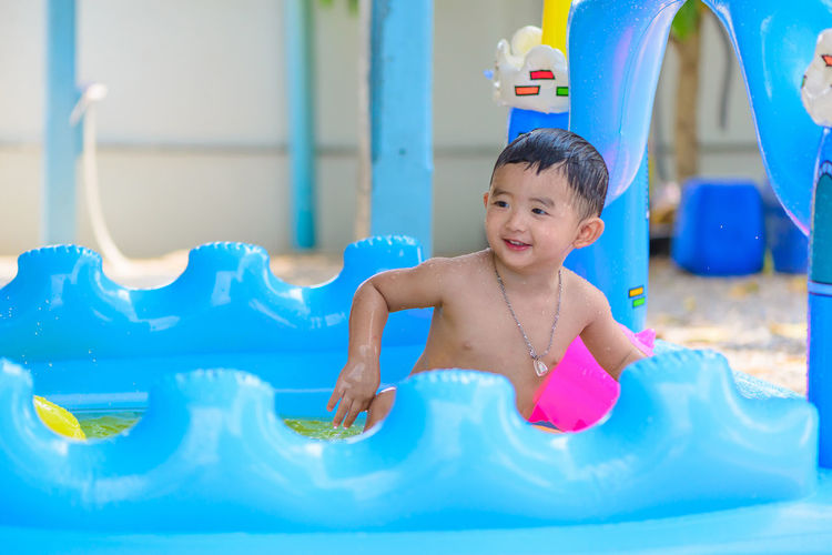 Happy cute boy playing in wading pool