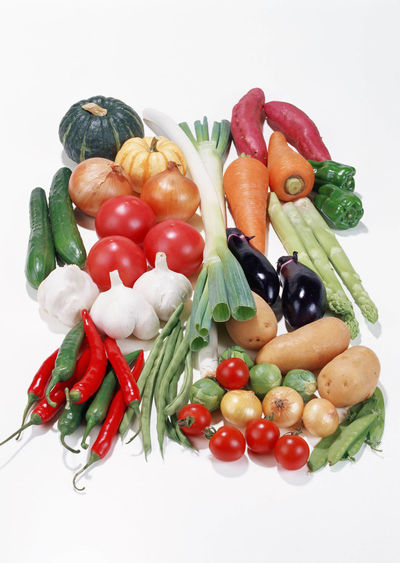 Tomatoes and vegetables on white background