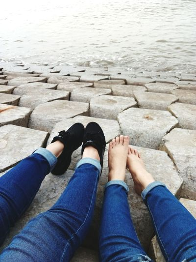 Low section of women sitting by sea