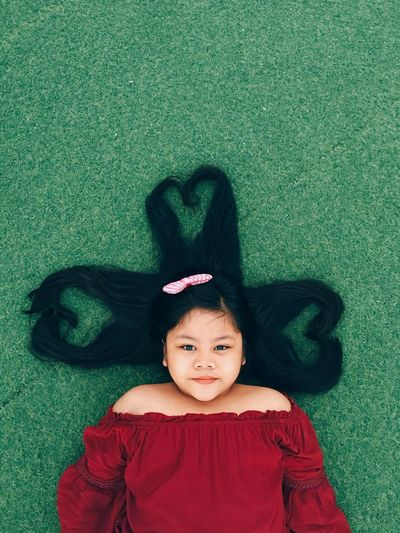 Girl with heart shape made of hair while lying on grassy field