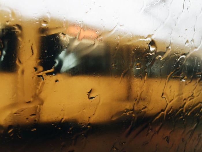 Road seen through wet car window