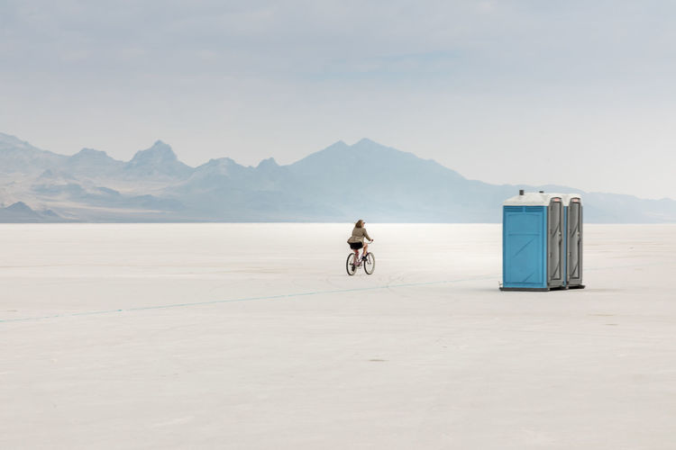 Woman cycling on salt flat against sky