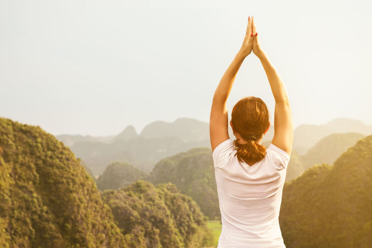 Rear view of woman practicing yoga against mountains during foggy weather