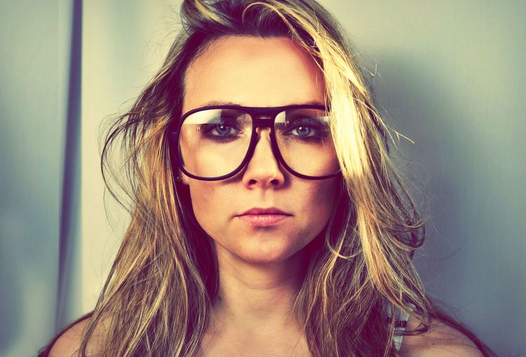 Portrait of blond woman with retro eyeglasses against wall