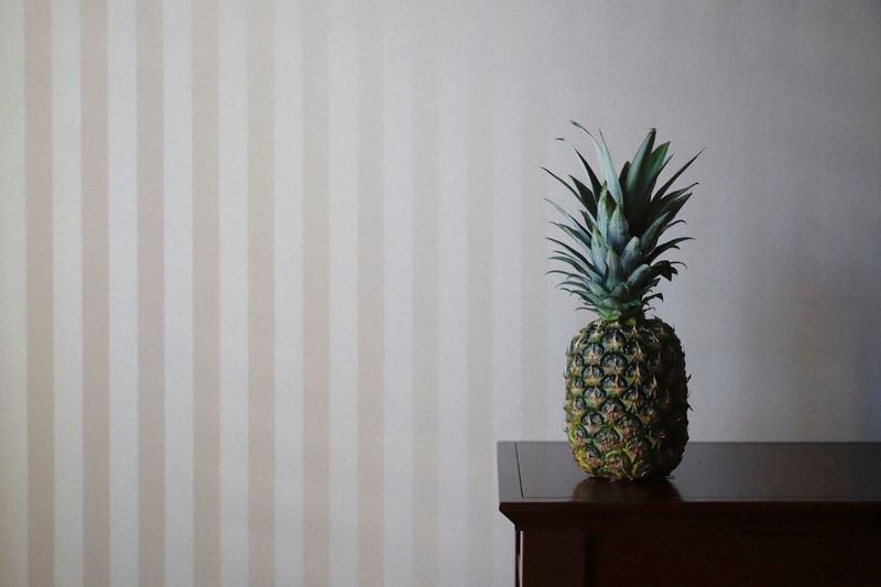 Close-up of pineapple on table against wall at home