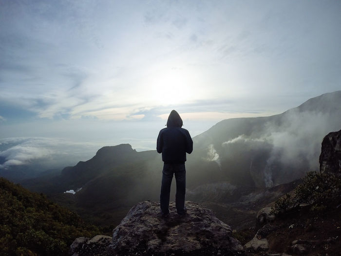 Full length rear view of man standing on top of mountain