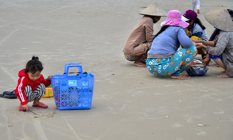 Wait for mother to sell at beach Adult Beach Child Cute Day Docile Females Full Length Hat Ke Ga Cape Ke Ga, Viet Nam Marketplace Multi Colored Outdoors People Plastic Sandals Plastic Sandals Playing Alone Sell And Buy Shy Sitting Social Issues Streetphotography Trade Women